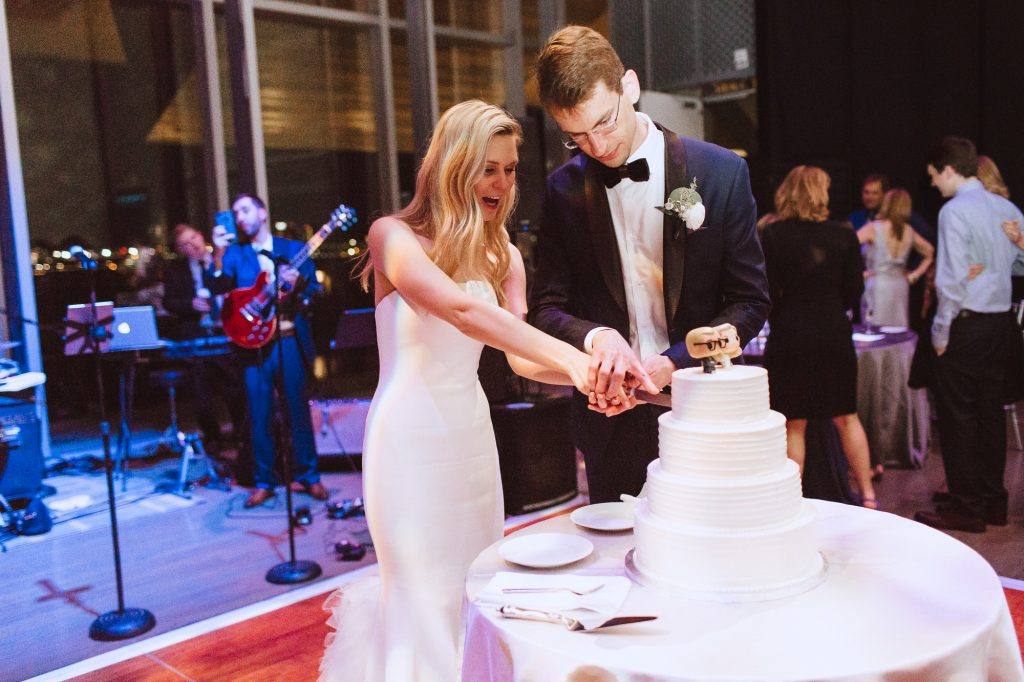 bride and groom cut a modern wedding cake at the ICA museum in Boston for a modern wedding