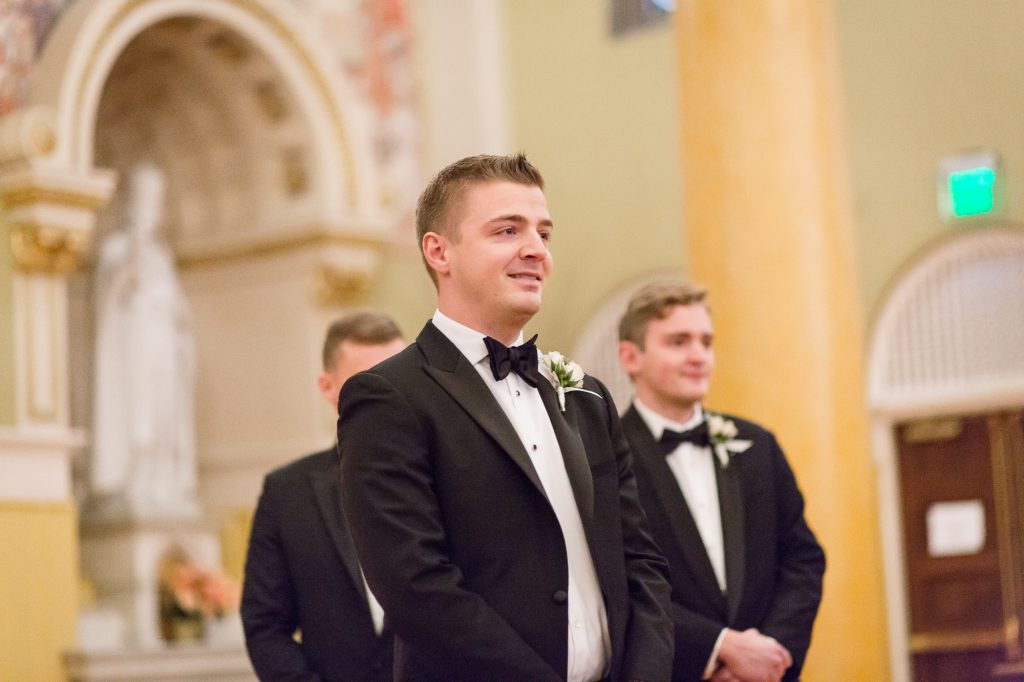 groom watching his bride down the aisle in church at a Saint Cecilia Boston wedding
