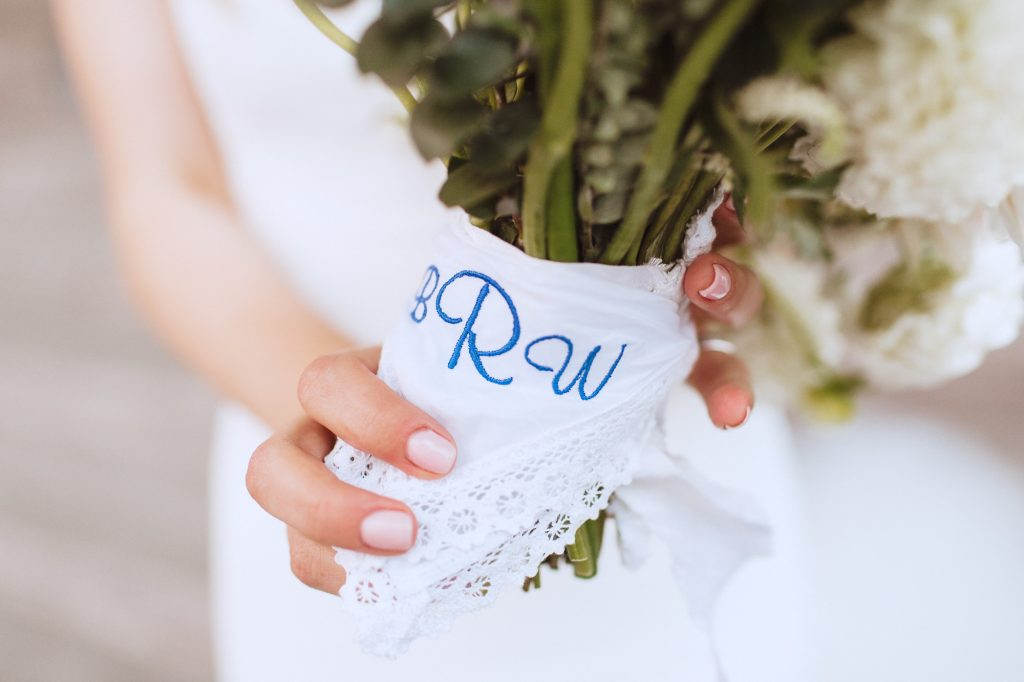 adorable wedding details such as a handkerchief around a bride's bouquet