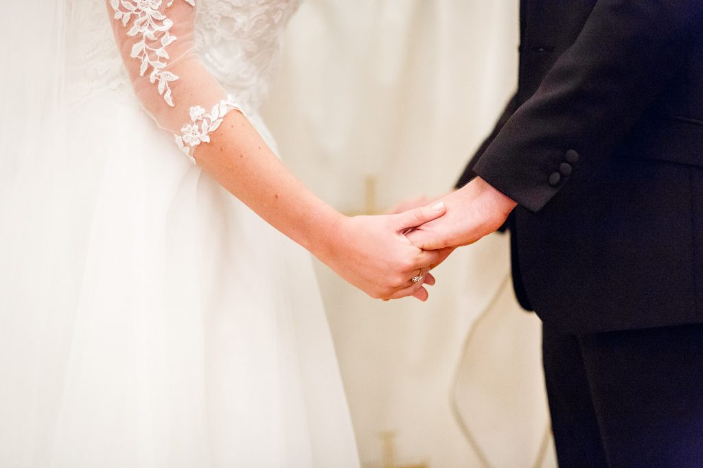 bride and groom holding hands at their catholic wedding ceremony in Boston